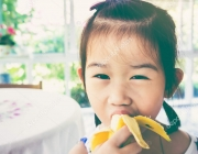 Adorable asian girl eating a ripe banana. vintage tone.