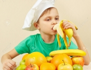 Little boy in chefs hat eat fresh banana at the table with fruits