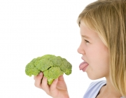 Young girl holding broccoli and sticking tongue out