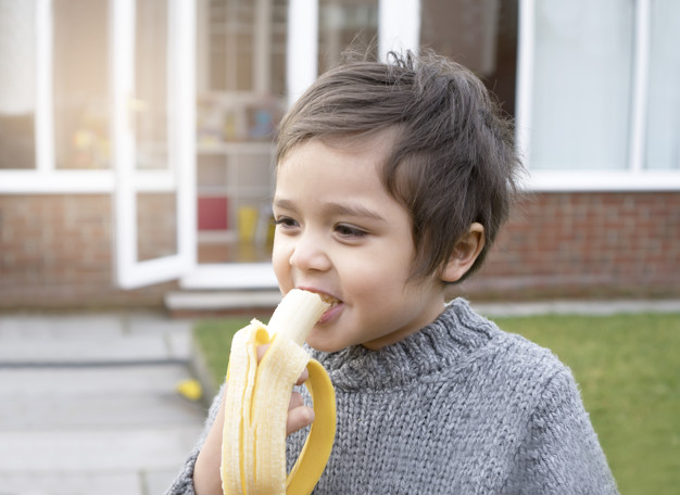 Healthy little boy eating banana with smiling face, Happy kid enjoy eating fresh fruit. Healthy food for children concept.