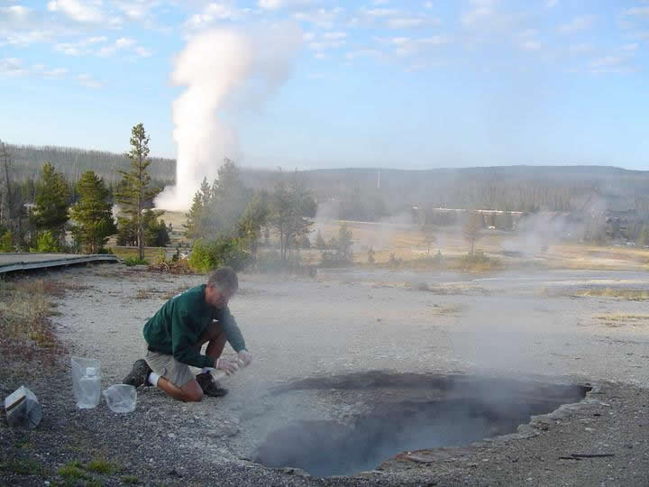 USGS Scientist Sampling Ear Spring, Wyoming. Old Faithful is Erupting in the Background