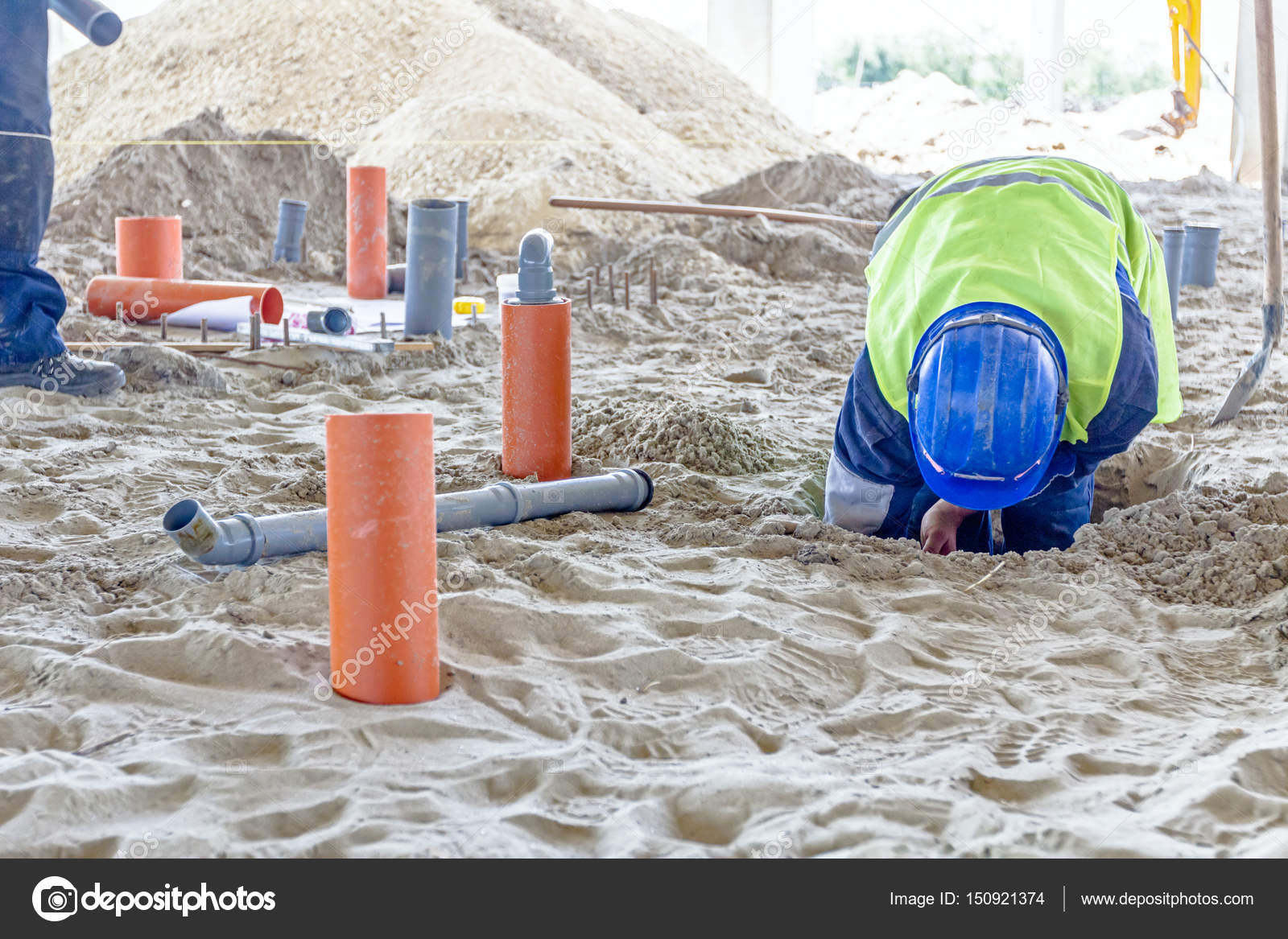 Construction worker is assembly pipeline in sandy soil