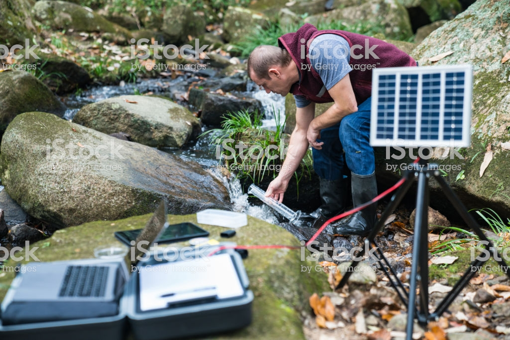 An environmental researcher monitoring water quality from a solar powered field laboratory